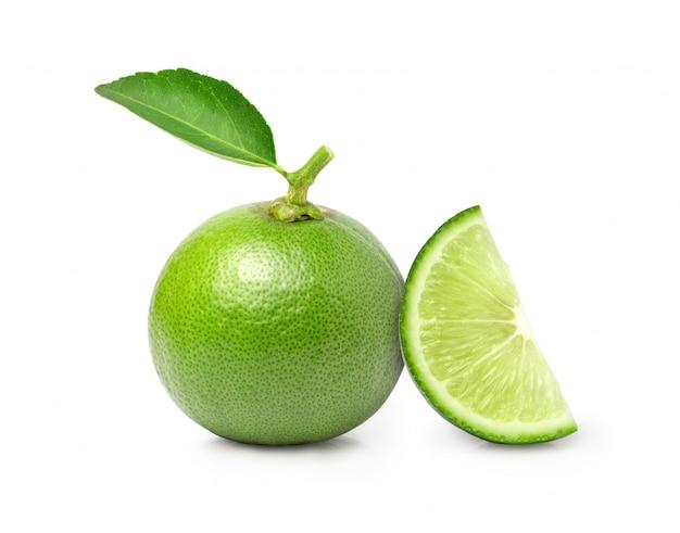 Плоды зеленого лайма с листьями и нарезанным кусочком на белом фоне