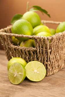 Green lime on old brown wooden table, lemon