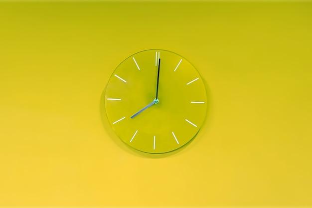 Зеленые лаймовые круглые современные аналоговые стеклянные часы висят на светло-желто-зеленой стене. показывает текущее время восемь.