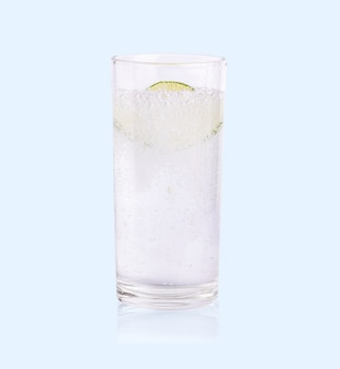 Green lime sliced falling in the soda water of glass on the soft blue