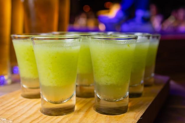 カウンターに立っているショットグラスの緑色の液体。