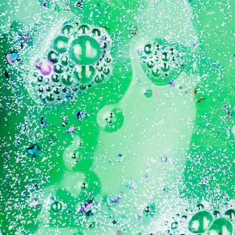 Green liquid with silver crumbs