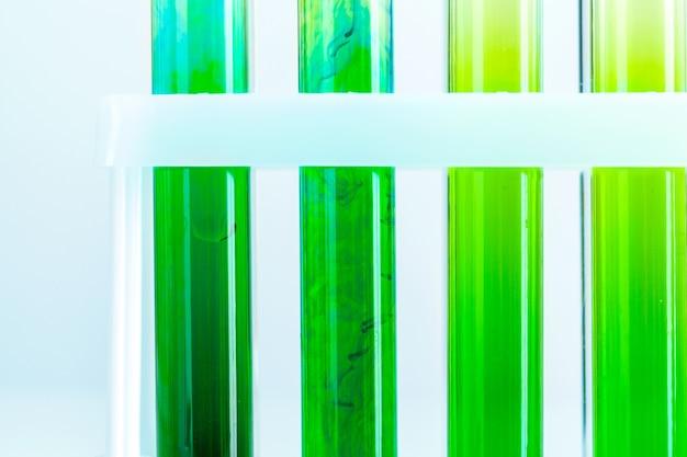 화학 실험실에서 시험관에 있는 녹색 액체를 닫습니다.