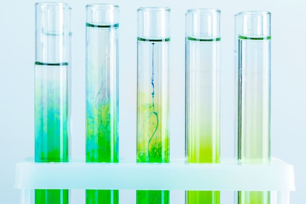Green liquids in test tubes in chemical laboratory close up