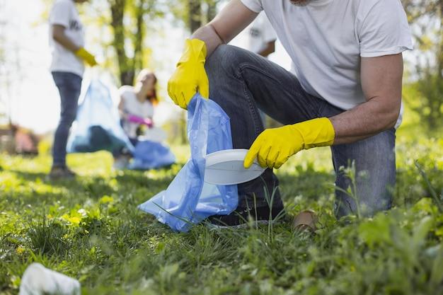 Зеленая жизнь. крупным планом мужские руки в желтых перчатках и с мешком для мусора