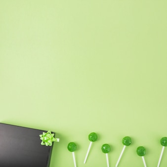Green lollipops with black gift box and bow on green background