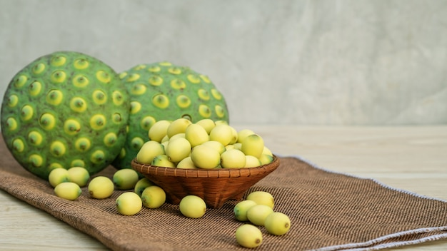 Green lotus seeds on a wooden table.