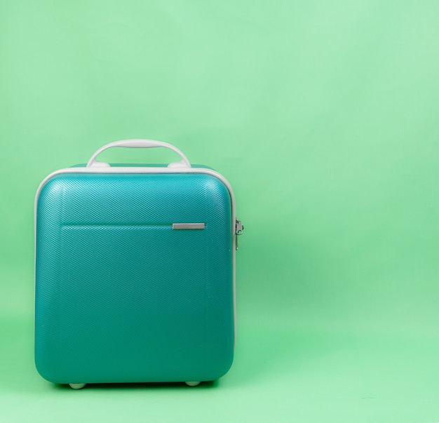 Green luggage for travel on green background