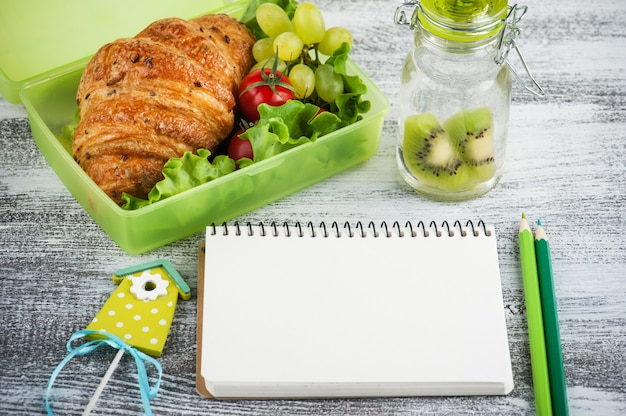 Green lunch box with croissant and salad