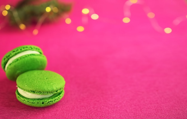 Green macaron with fondant on red paper background. near a branch of a christmas tree with a garland. close-up, copyspace.