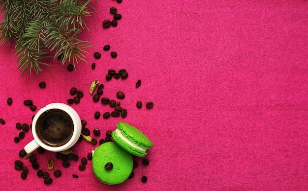Green macaron with fondant on a red paper background. nearby is a cup of espresso, roasted coffee grains. christmas tree branch. close-up, copyspace.