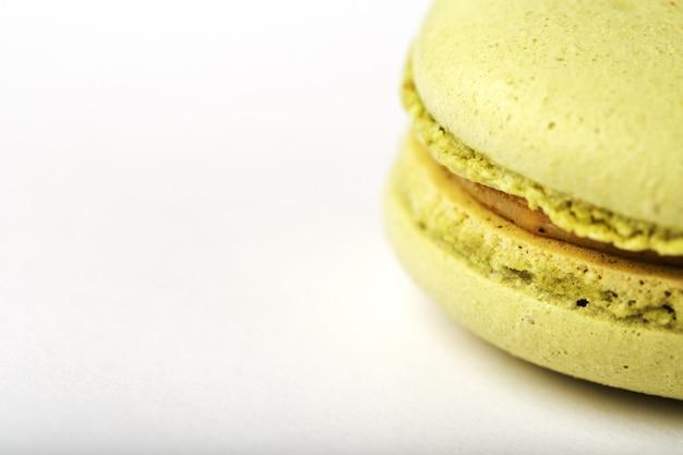 Зеленые печенья макарон на белой изолированной предпосылке ,.
