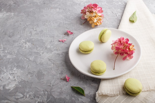 Green macarons or macaroons cakes on white ceramic plate on a gray concrete background  side view.