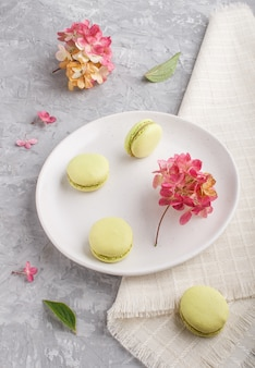 Green macarons or macaroons cakes on white ceramic plate on a gray concrete, side view.