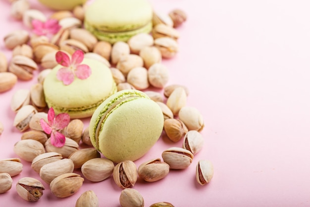 Green macarons or macaroons cakes with pistache nuts. side view, copy space.