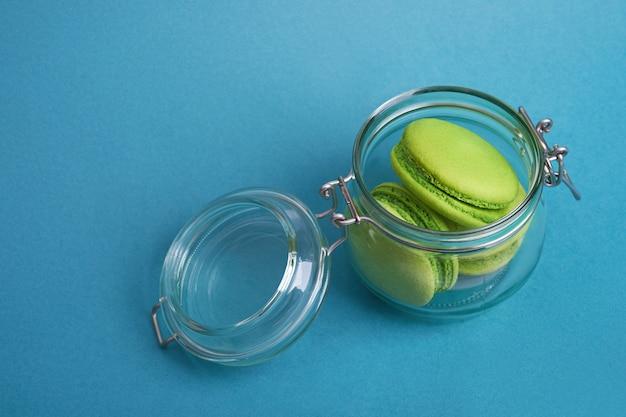 ガラスの瓶の青い背景に緑のマカロン