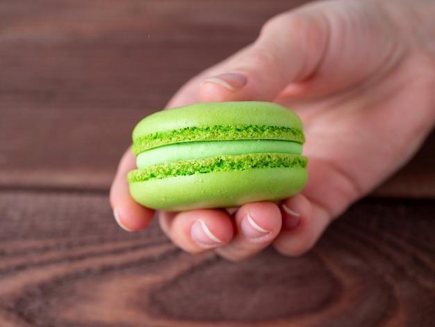 私の手に緑のマカロン。木製の背景。おいしい甘いデザート。