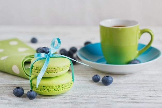 白い木製のテーブルにブルーベリーと緑のマカロン