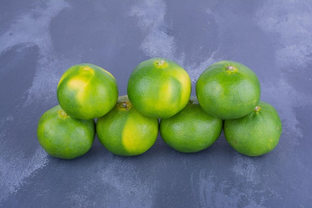 Mandarini verdi sulla tavola blu nella riga geometrica.