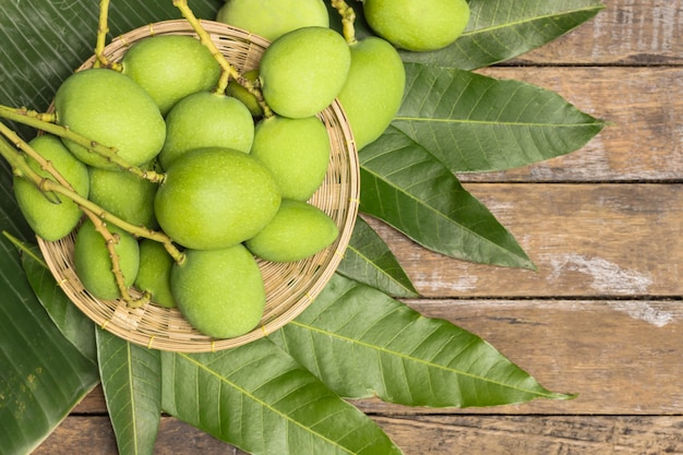Green mangoes in basket and leaves on wooden floor free space.