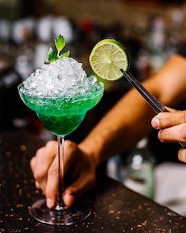Vista laterale della calce verde menta del liquore del midori della margarita
