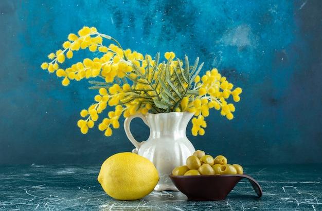 Зеленые маринованные оливки в черной чашке с лимоном в сторону. фото высокого качества