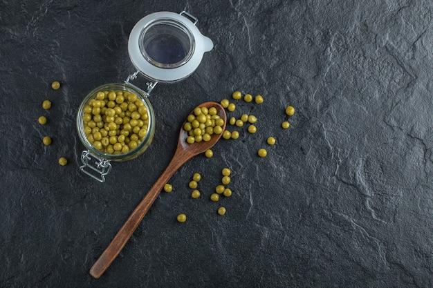 瓶と地面にグリーンマリネしたエンドウ豆。