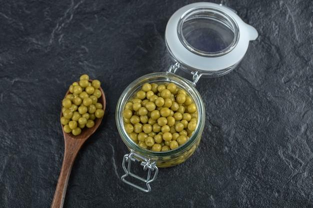 グリーンマリネしたエンドウ豆。瓶と木のスプーン。