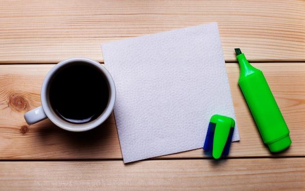 Зеленый маркер, чашка кофе и белая салфетка на деревянном столе. фон для текста.