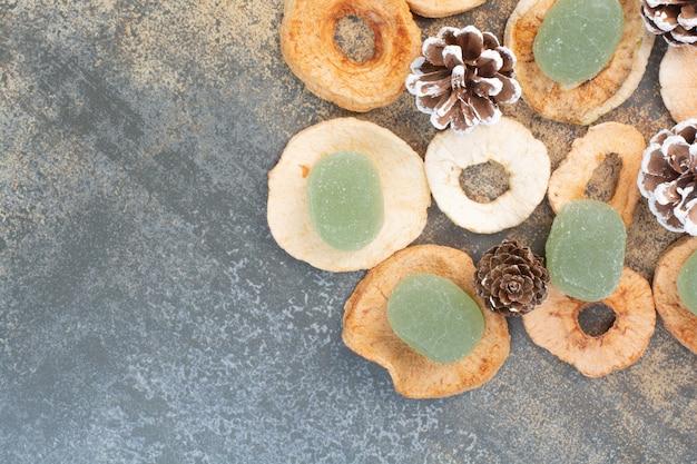 Зеленый мармелад с сухофруктами и шишками на мраморном фоне. фото высокого качества