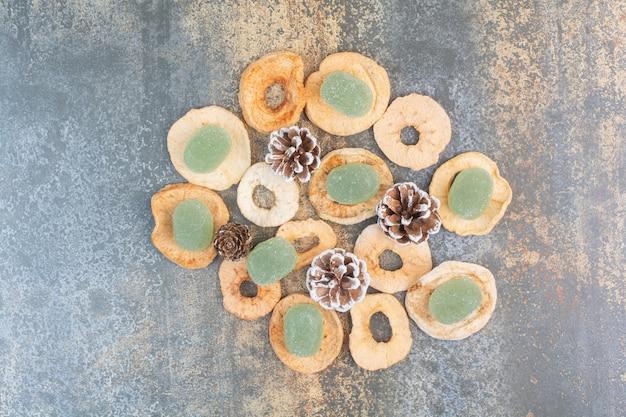 말린 과일과 솔방울 대리석 배경에 녹색 마멀레이드. 고품질 사진