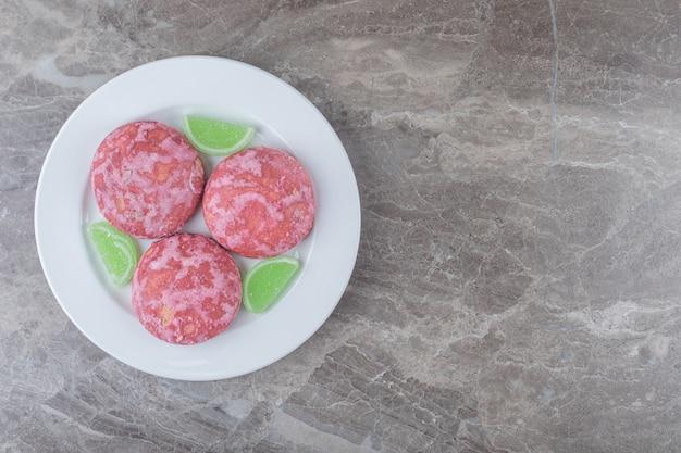 大理石の表面の大皿に緑のマーマレードとピンクのクッキー