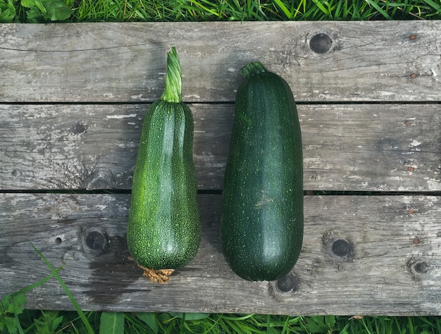 Green marrows on a wooden surface