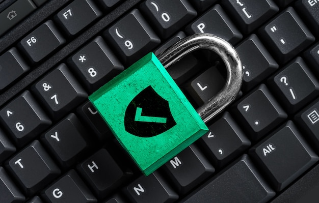 Green master key on black keyboard, computer security privacy concept