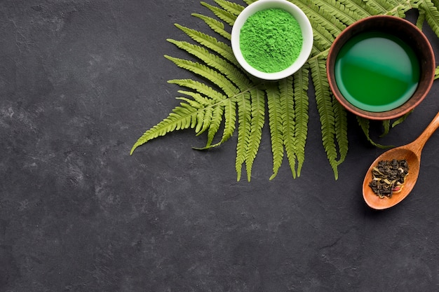 Green match tea and dry herb with fern leaves on black textured background