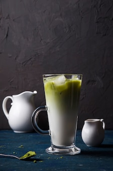 Green matcha powder milk and ice tea summer drink