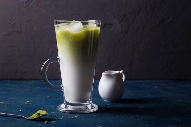 Green matcha powder milk and ice tea summer drink