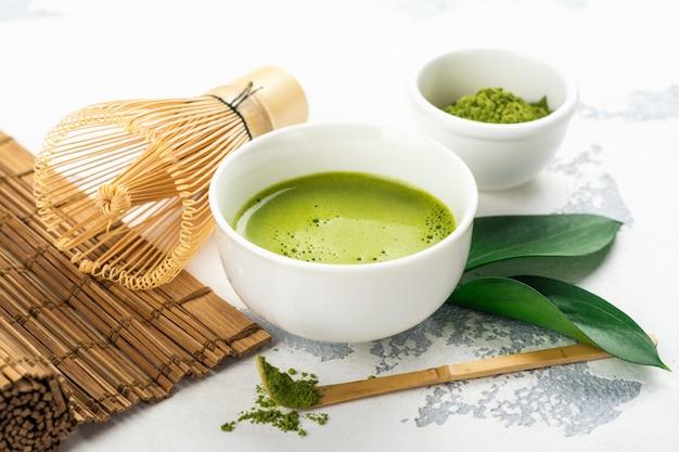 Зеленый чай с напитком матча и чайные аксессуары на белом фоне