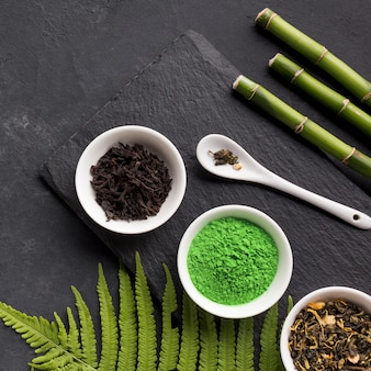 Green matcha tea and dry tea herb with bamboo stick over black stone background
