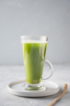 Green matcha tea in latte glass on grey table.