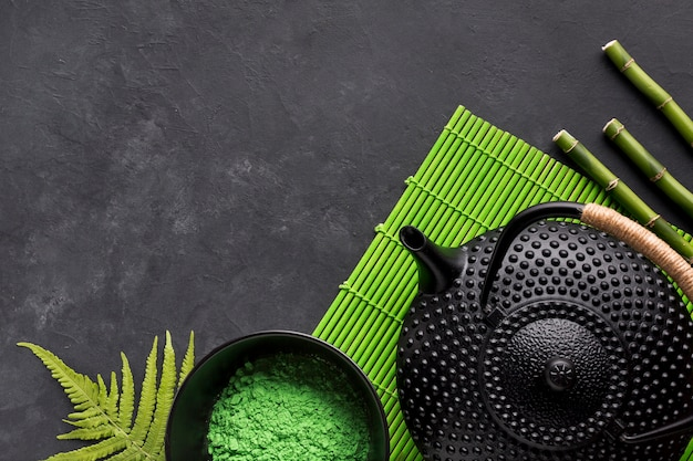 Green matcha tea powder and black teapot on placemat