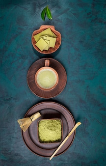 Green matcha tea, powder and chocolate in brown ceramic utensil laid out on emerald backdrop.