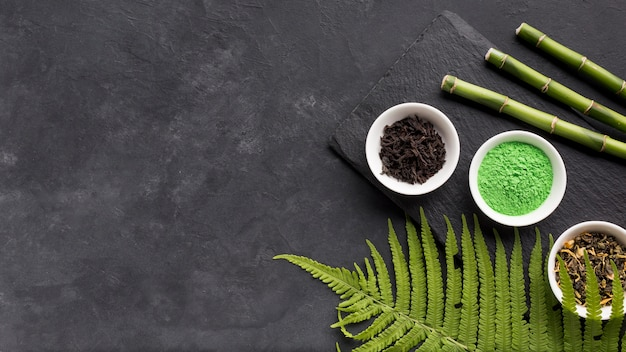 Green matcha tea powder and dry herb with bamboo stick on black textured surface