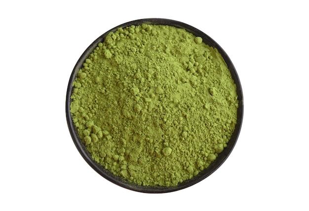 Порошок зеленого чая матча в черной миске, изолированной на белом