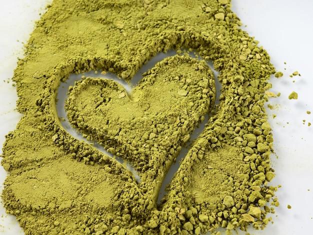 심장 모양으로 흰색 배경에 녹색 말 차 가루. 건강의 개념입니다.