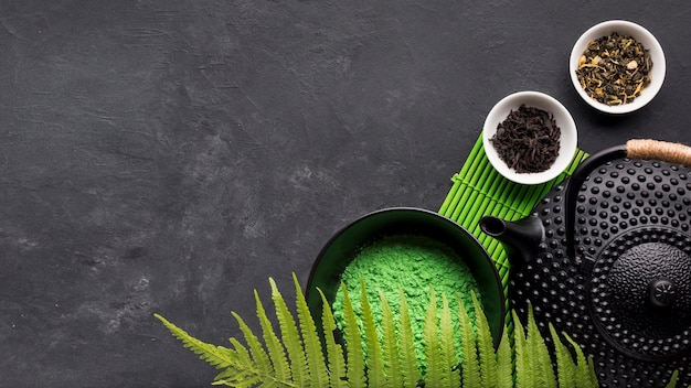 Green matcha tea powder with dry herb on black background