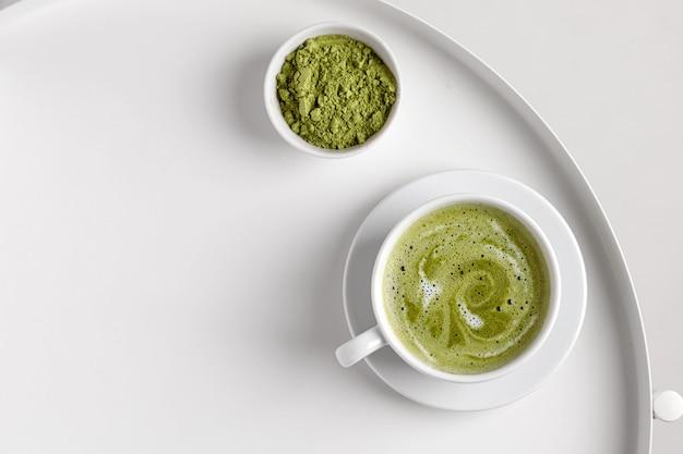 白いテーブルと白い背景の上のカップにミルクと緑の抹茶