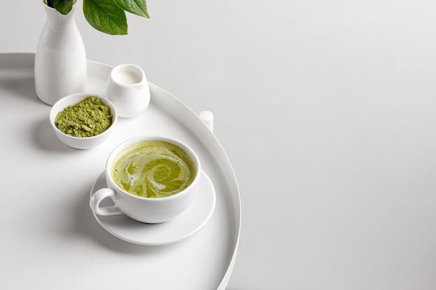 흰색 테이블과 흰색 backgriund에 컵에 우유와 녹색 말 차
