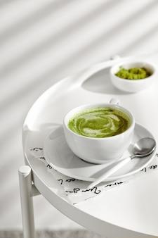흰색 테이블에 숟가락이 있는 컵에 우유를 넣은 녹차