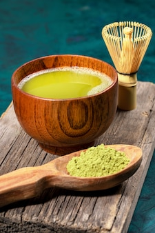 Green matcha tea in wooden cup, spoon with powder and whisk on old wooden board on emerald background. vertical photo.